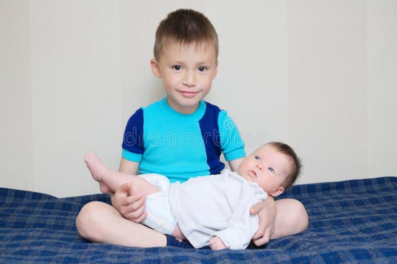 Bruder, der die kleine neugeborene Schwester zu Hause liegt auf seinen Beinen hält stockfotos