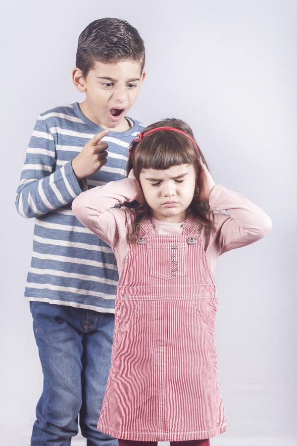 Bruder, der mit seiner kleinen Schwester argumentiert stockbild