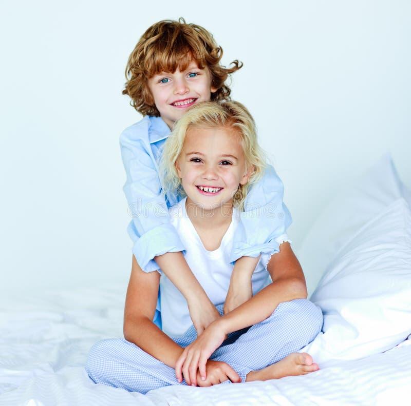 Bruder, der seine gute Nacht der Schwester umarmt lizenzfreie stockfotos