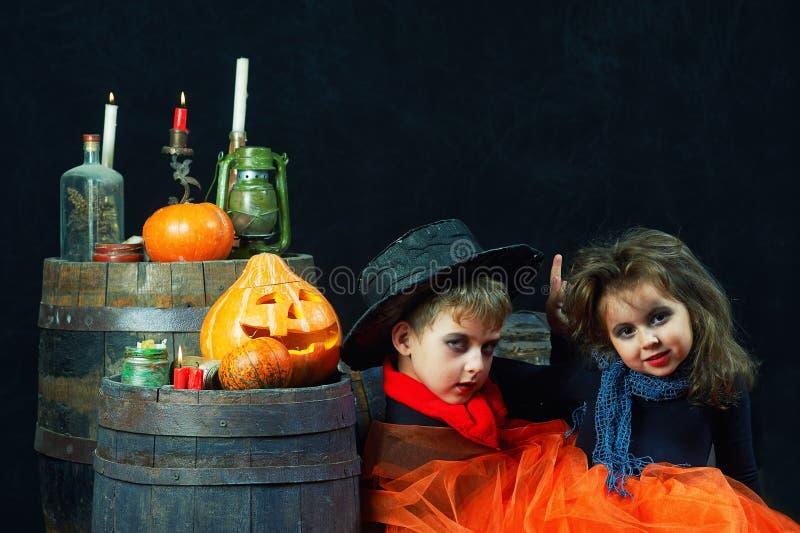 Bruder und Schwester auf Halloween Lustige Kinder in den Karnevalskostümen auf dunklem Hintergrund stockfotografie