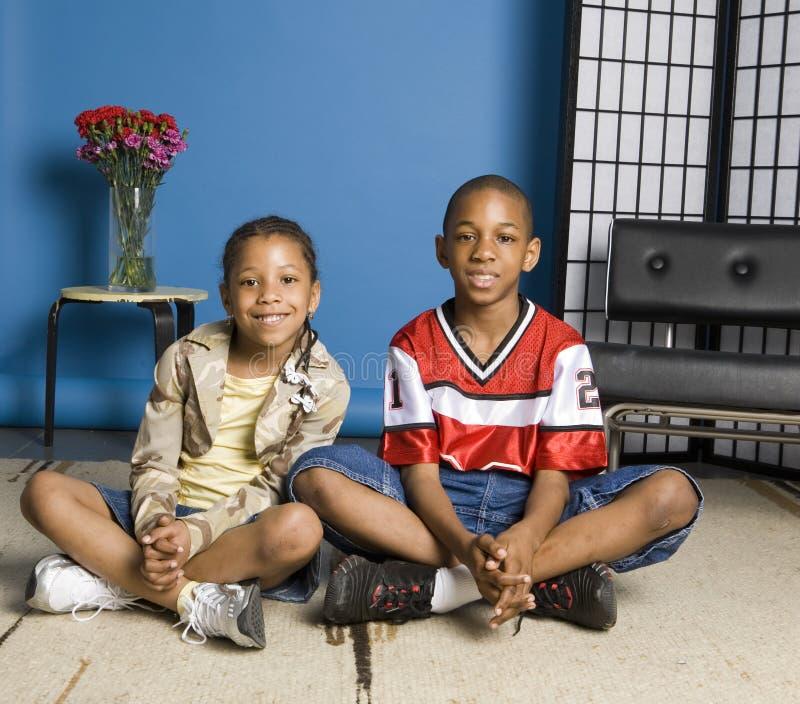 Bruder und Schwester, die auf dem Fußboden sitzen stockbild