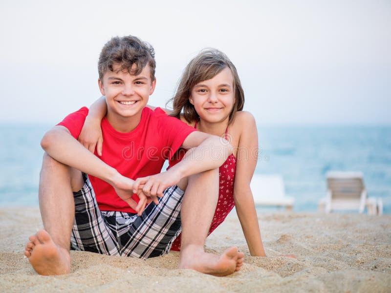 Bruder und Schwester, die auf Strand spielen lizenzfreie stockfotografie