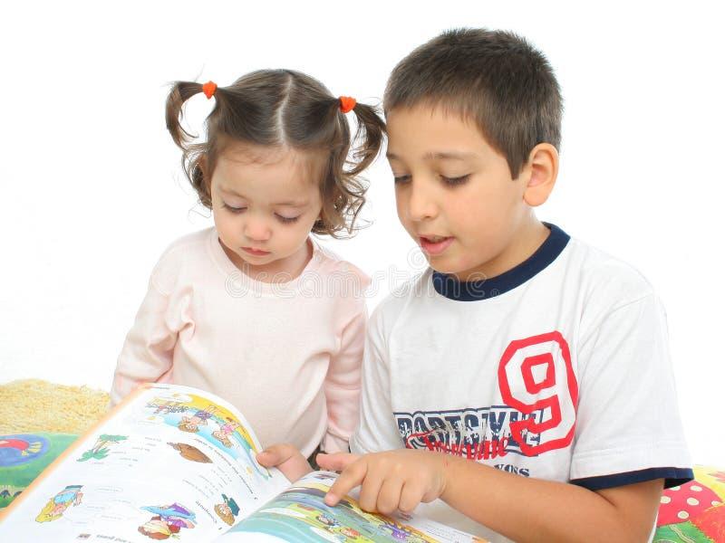 Bruder und Schwester, die ein Buch auf dem Fußboden lesen lizenzfreie stockfotografie