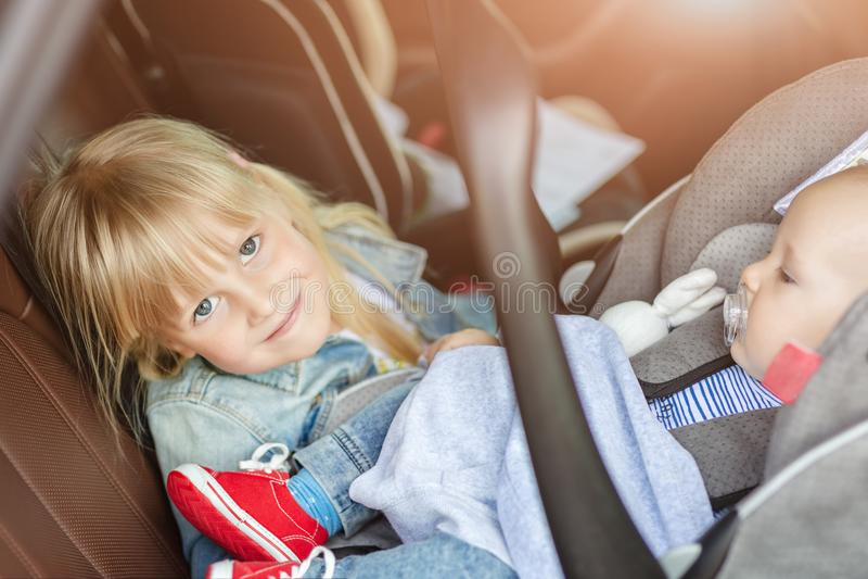 Bruder und Schwester, die im Auto im Sicherheitssitz sitzen Geschwister auf den Passagierplätzen, die Spaß zusammen während der R stockfotos