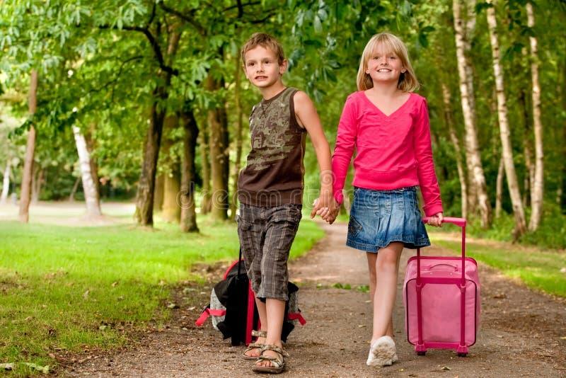 Bruder und Schwester, die mit therir Koffern gehen lizenzfreie stockfotos