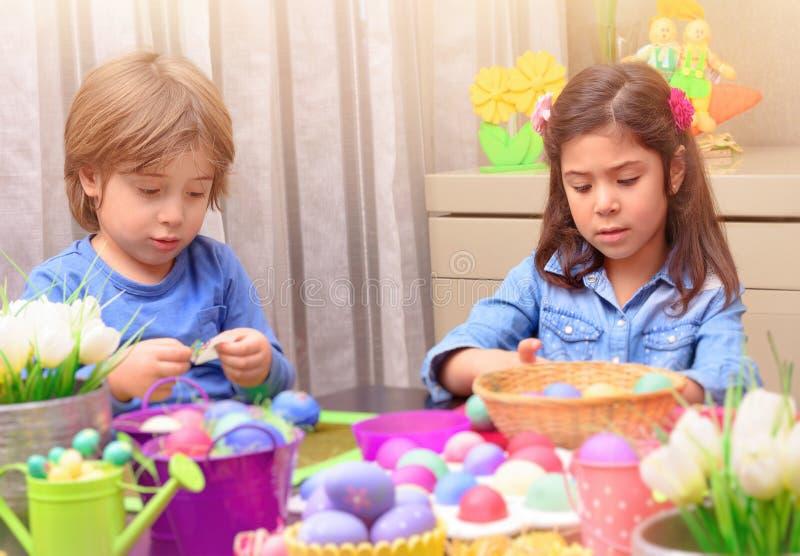 Bruder und Schwester, die Ostereier färben stockbild