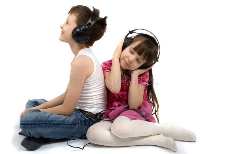 Bruder und Schwester, die zu den Kopfhörern hören stockbild