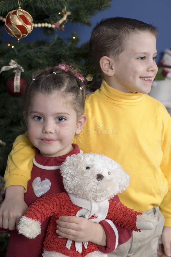 Bruder und Schwester durch einen Weihnachtsbaum lizenzfreie stockfotos