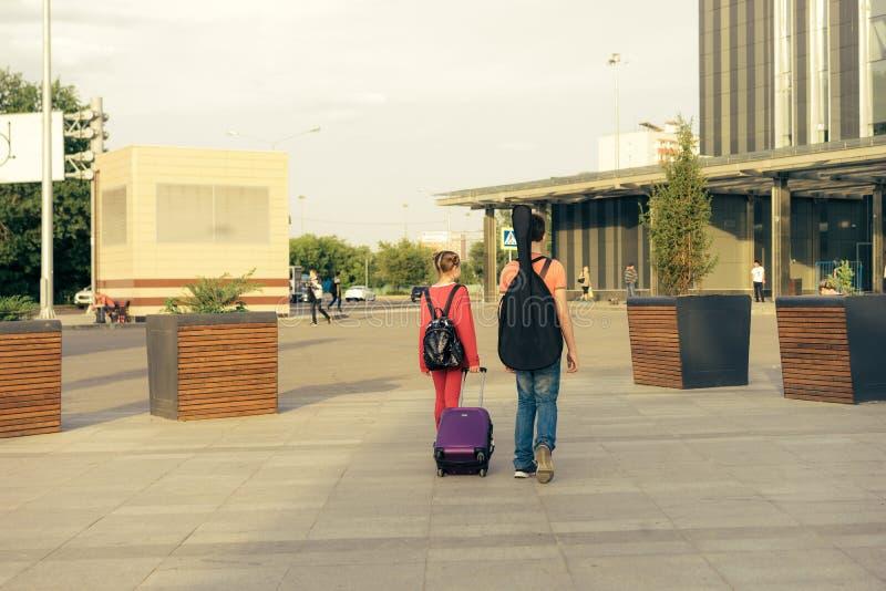 Bruder und Schwester mit einem Koffer, einem Rucksack und einer Gitarre gehen zur Station stockfoto