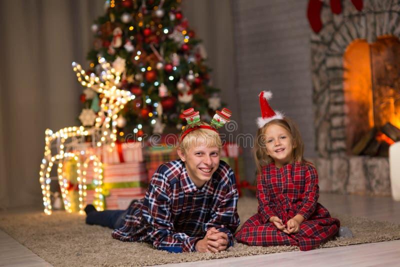 Bruder und Schwester nahe dem Weihnachtsbaum stockbild