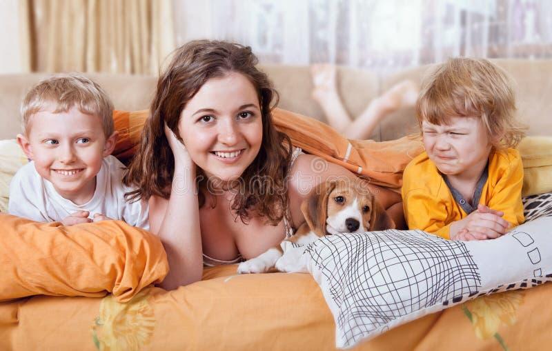 Bruder und Schwestern im Bett mit Welpen lizenzfreie stockfotos
