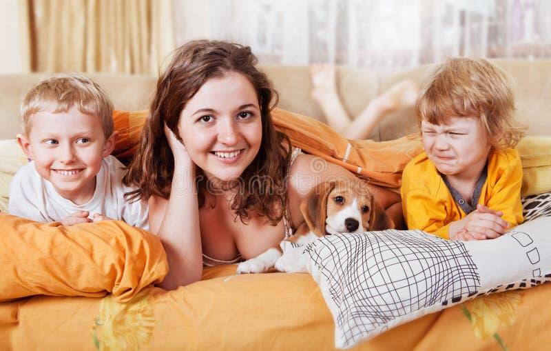 Bruder und Schwestern im Bett mit Welpen stockfotos