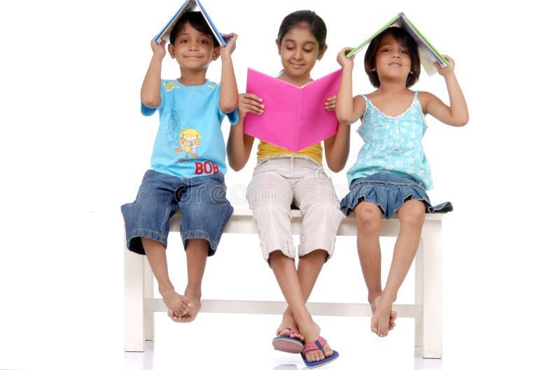 Bruder und zwei Schwestern, die Bücher anhalten stockbilder
