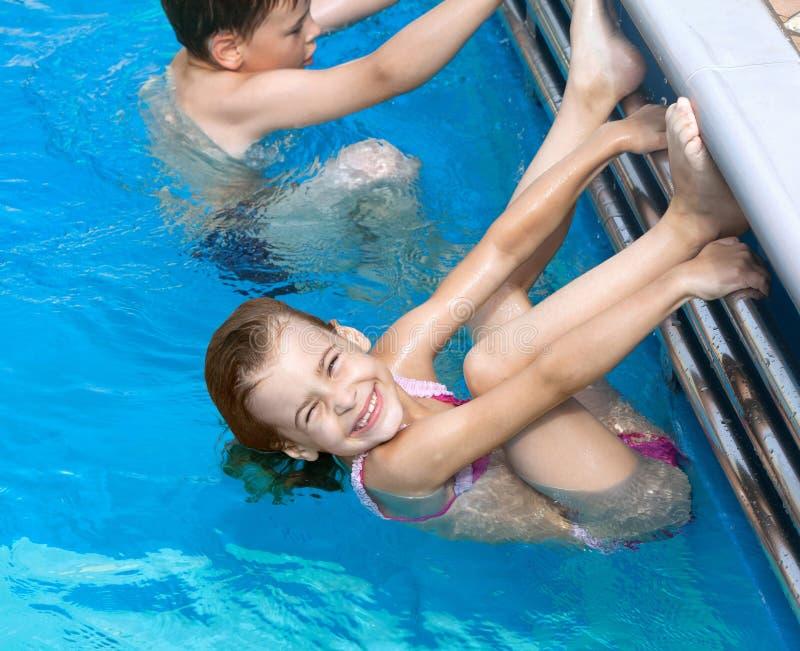 Bruderschwester, die Übungen im Pool tut stockfotografie