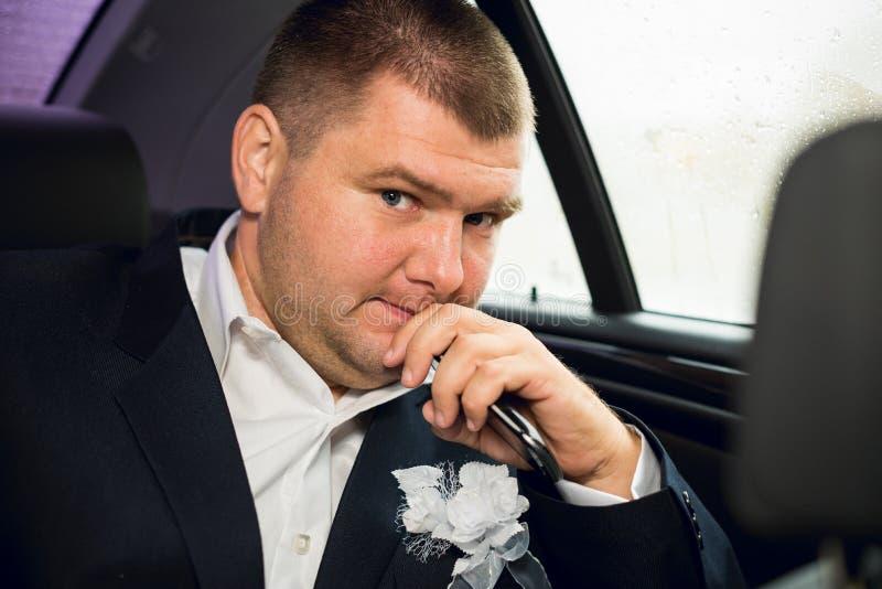 Brudgum i bilen royaltyfri foto