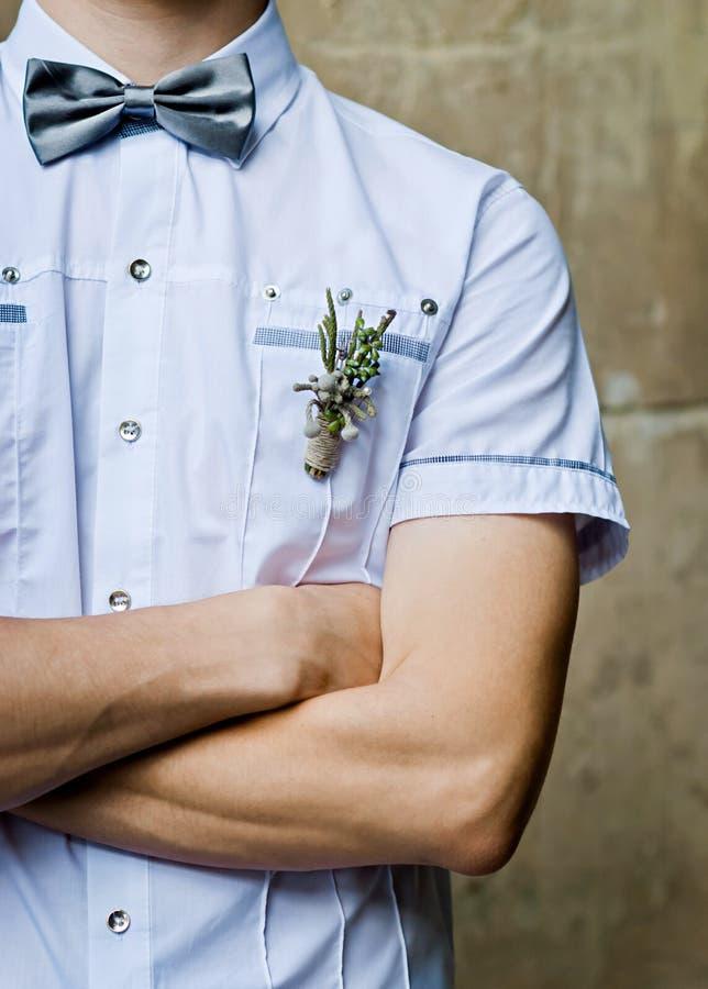 Brudgum i den vita skjortan och flugan hans vikta armar royaltyfria foton