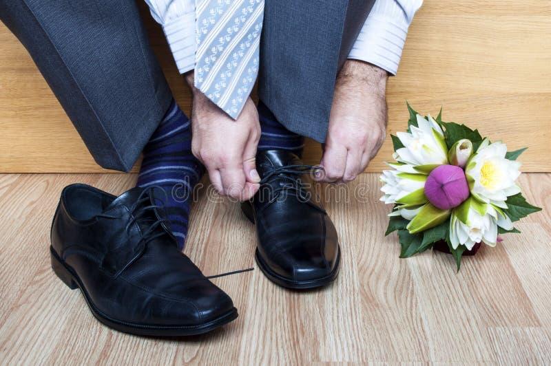 Brudgum i dräkten som binder skor arkivbild