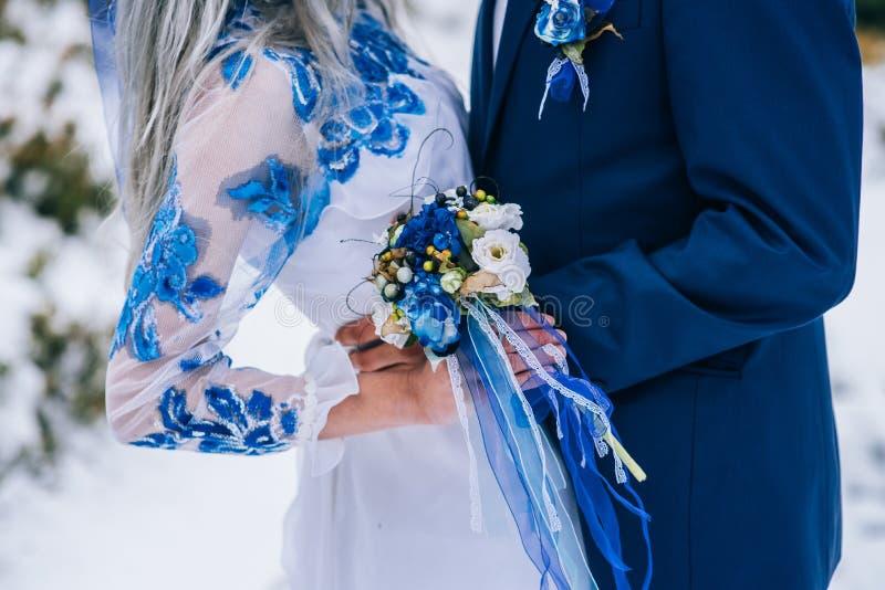 Brudgum i en blå dräkt och brud i vit i bergen Carpath arkivbild