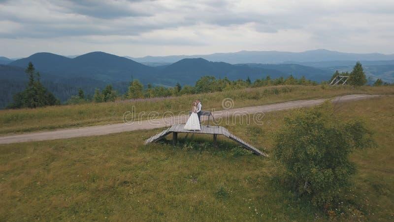 Brudgum med bruden tillsammans på kullar för ett berg Flyg- surrskott arkivfoto