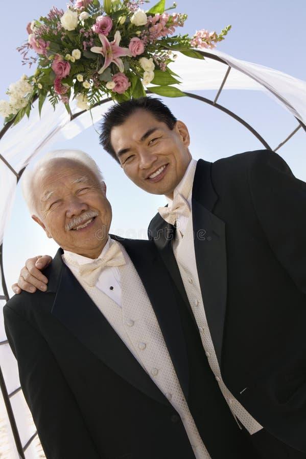 Brudgum med fadern under valvgång utomhus (ståenden) royaltyfri foto