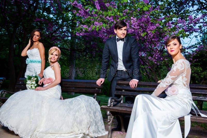 Brudgum med tre brudar fotografering för bildbyråer