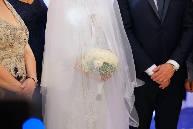 Brudgum och anseendet och rymma en bukett av vita blommor Fokus på en brud- bukett royaltyfri foto