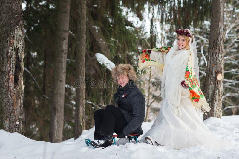 Brudgum och brud i den kalla vinterskogen med den stora träsläden royaltyfri foto