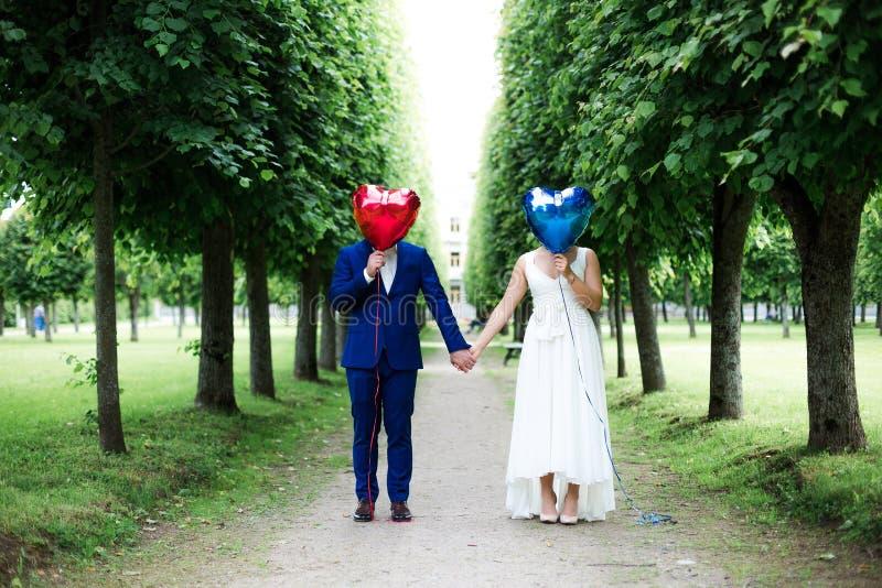 Brudgum och brud med ballonger på trottoaren royaltyfri bild