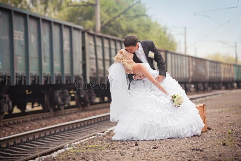 Brudgum och brud med en resväska på järnvägsstationen arkivbild