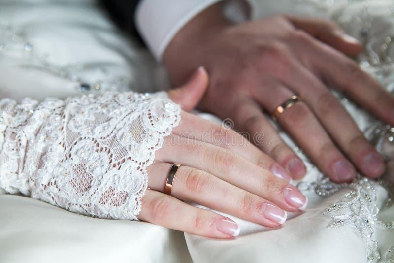 Brudgum och brud som rymmer händer med vigselringar arkivfoton