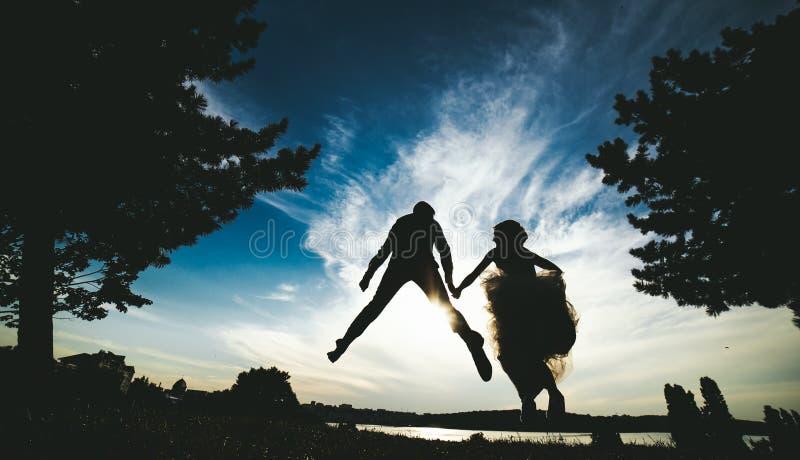 Brudgum- och brudbanhoppning mot den härliga himlen fotografering för bildbyråer