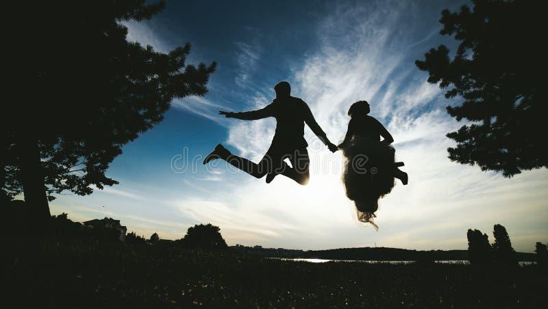 Brudgum- och brudbanhoppning mot den härliga himlen royaltyfri fotografi
