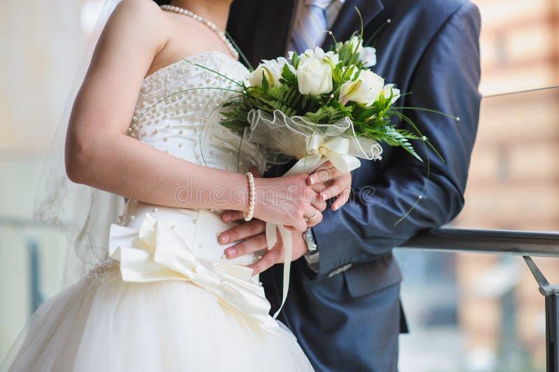 Brudgum och bruden med en bukett royaltyfria bilder
