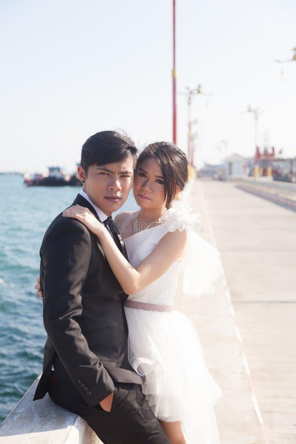 Brudgum- och brudsammanträde på trottoaren royaltyfri bild