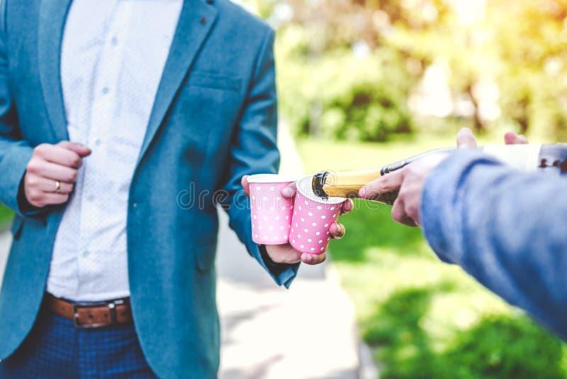Brudgum som är utomhus- med champagne på bröllopberöm royaltyfri bild