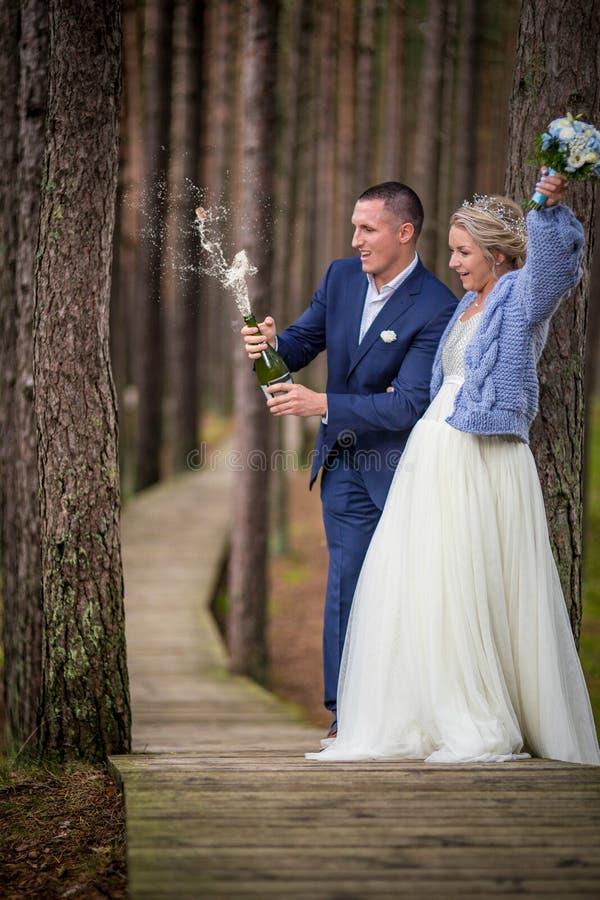 Brudgum som öppnar champagnen på bröllopdagen fotografering för bildbyråer