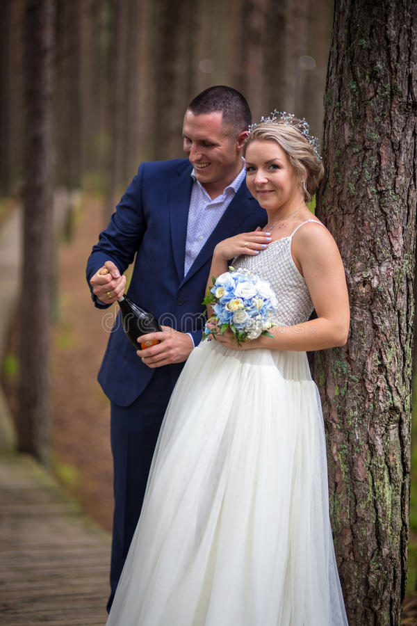 Brudgum som öppnar champagnen på bröllopdagen arkivbilder