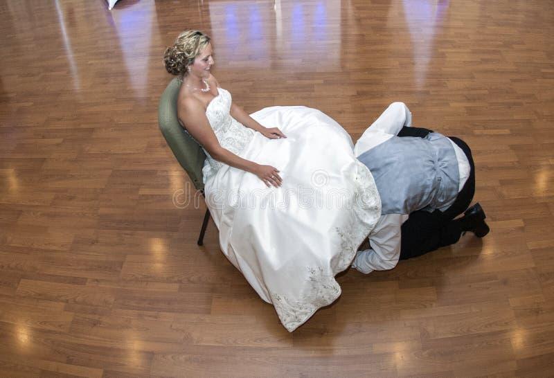 Brudgum som av tar strumpebandet royaltyfri foto