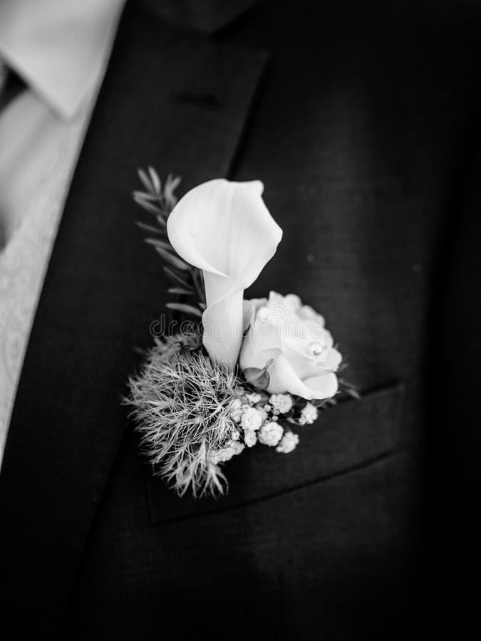Brudgum som bär i mörker - blå formell dräkt med elegant boutonniere från blomman för callalilja arkivbild