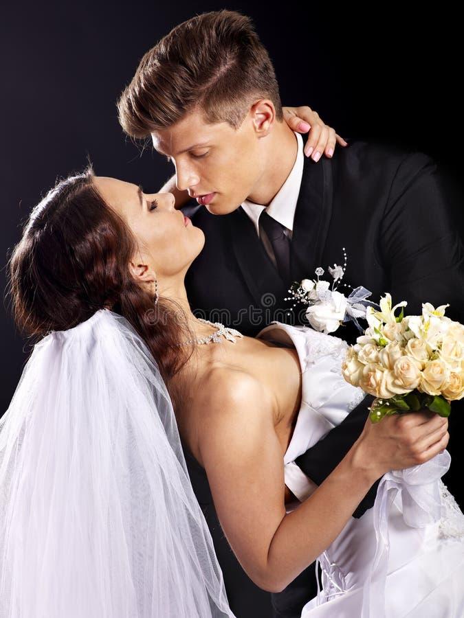 Brudgum som omfamnar bruden. arkivbild