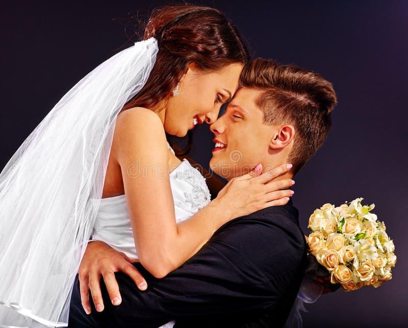 Brudgum som omfamnar bruden royaltyfria foton