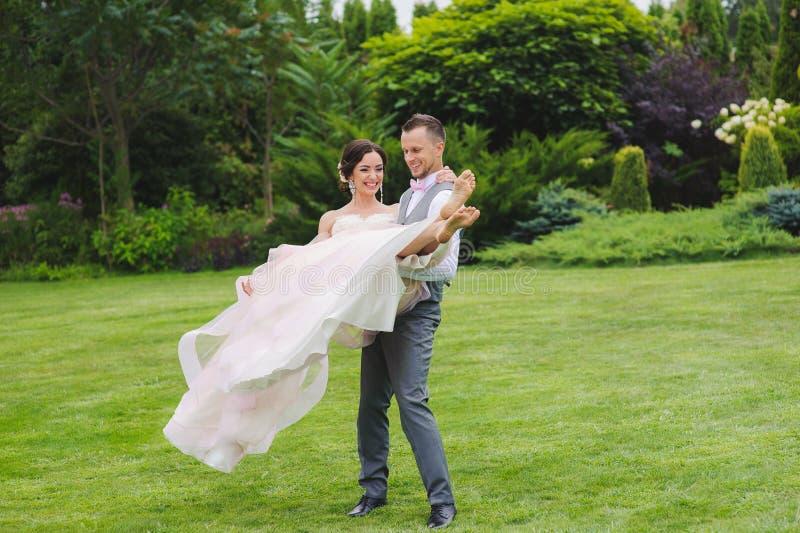 Brudgum som rymmer den härliga bruden i hans armar royaltyfri fotografi