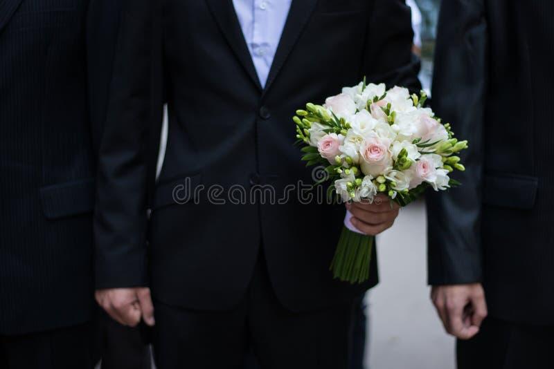 Brudgum som rymmer en bröllopbukett arkivbilder