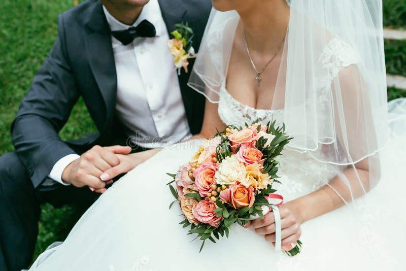 Brudgum som rymmer en brudhand med den weding buketten på bröllopdag royaltyfri foto