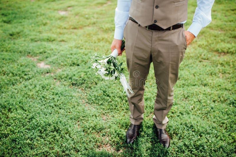 Brudgum som rymmer en bukett, brudgum med en bukett, bröllopdag arkivbild