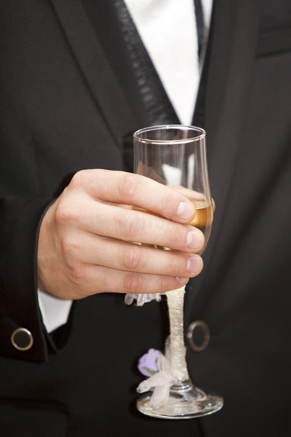 Brudgum som rymmer ett exponeringsglas med champagne fotografering för bildbyråer