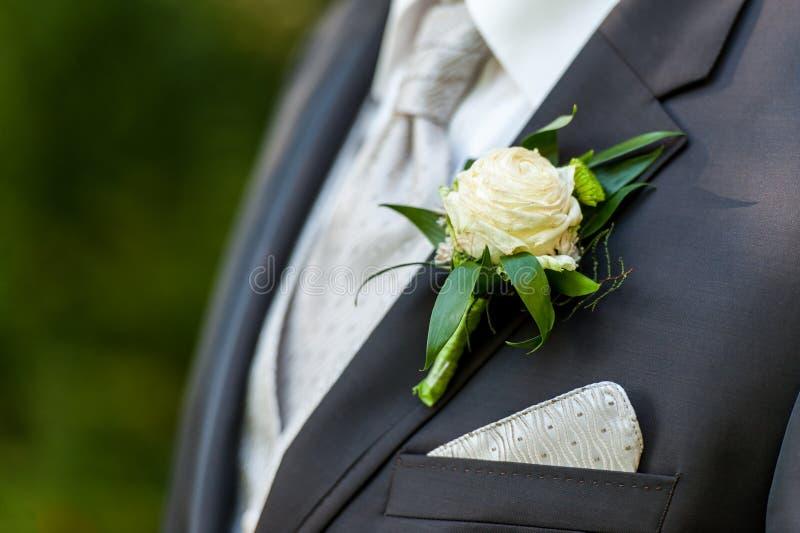 Brudgumfölje med blom- garnering arkivbilder