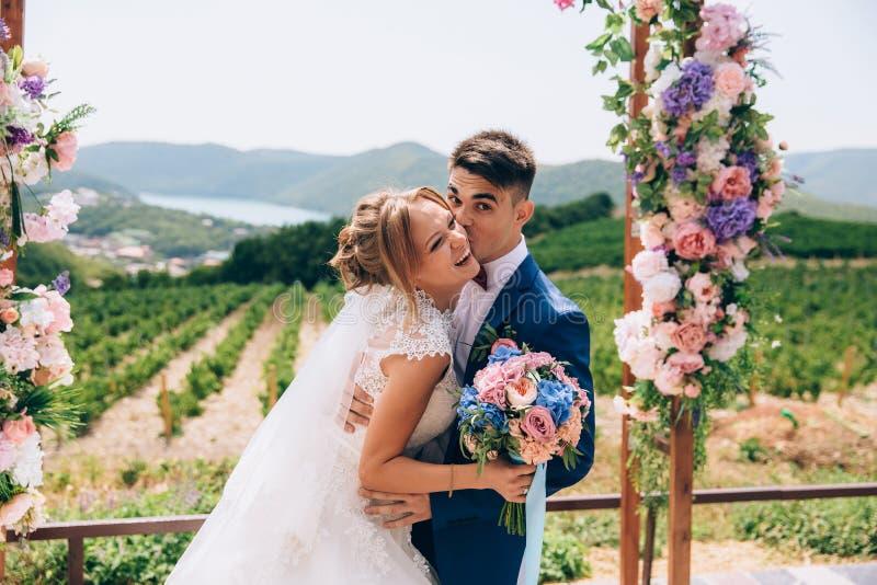 Brudgumkramarna och kysser hennes brud Flickan skrattar, därför att hon hörde ett bra skämt Vänner på bröllopet skämmer bort royaltyfri fotografi