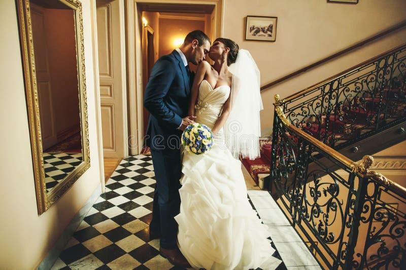 Brudgummen är den kyssande brudskuldran på bakgrundskorridoren med arkivbilder