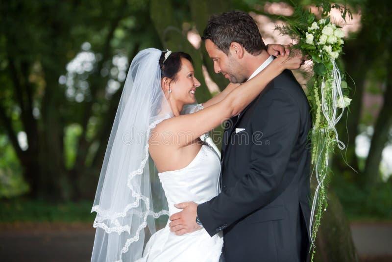 Bruden omfamnar hans brudgum arkivfoton